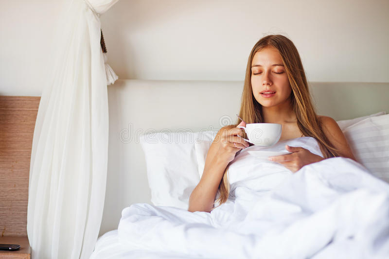 Donna che mangia caffè in un letto immagine stock libera da diritti