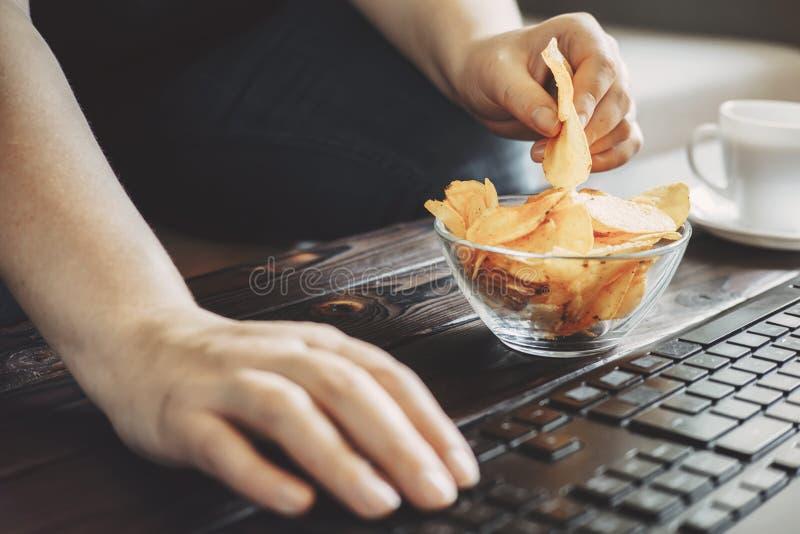 Donna che mangia i chip dalla ciotola nel suo luogo di lavoro fotografia stock