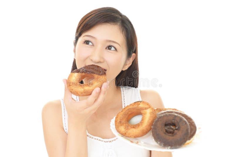 Donna che mangia i dolci immagini stock