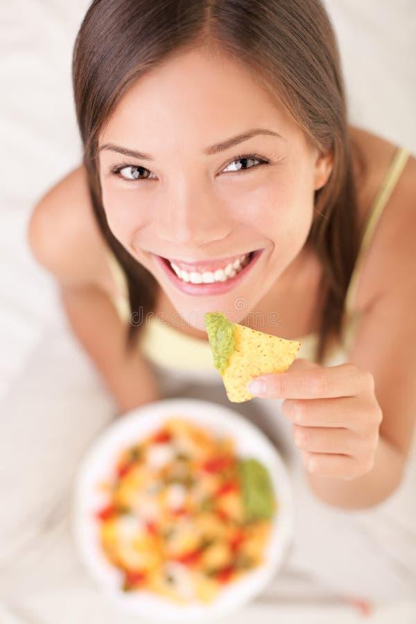 Donna che mangia i nachos immagine stock