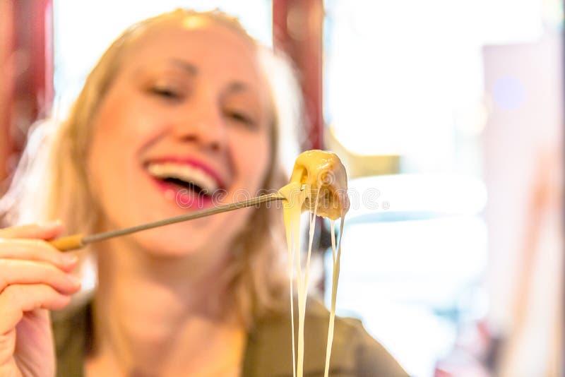 Donna che mangia il formaggio della fonduta fotografia stock
