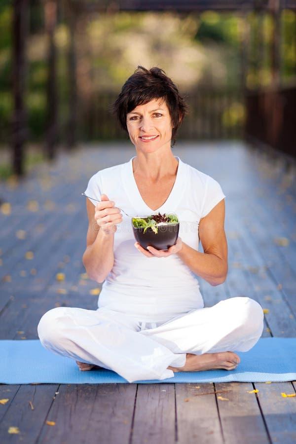 Donna che mangia insalata fotografia stock