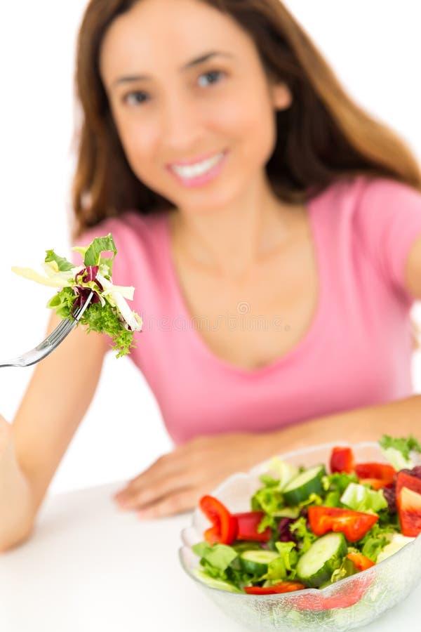 Donna che mangia insalata, fuoco sull'insalata fotografie stock