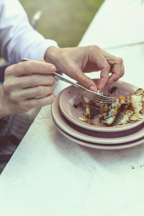 Donna che mangia la griglia del branzino Partito di estate nel cortile Colpo verticale fotografie stock libere da diritti