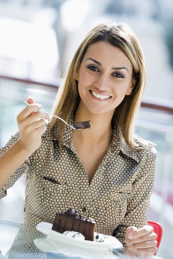 Donna che mangia la torta di cioccolato in caffè fotografia stock libera da diritti