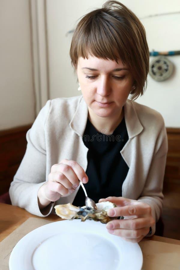Donna che mangia le ostriche fotografia stock