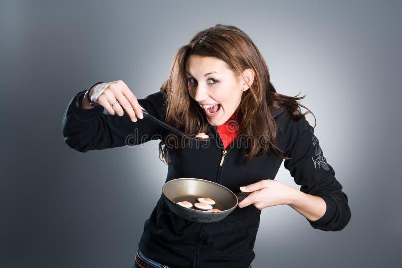 Donna che mangia le uova fotografia stock
