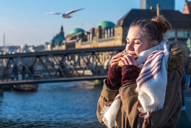 Donna che mangia lo spuntino tedesco del nord tradizionale del pesce di alimento immagine stock libera da diritti