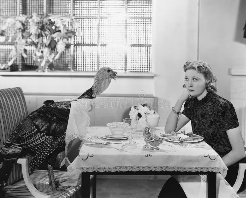 Donna che mangia pasto alla tavola con il tacchino vivo (tutte le persone rappresentate più lungamente non stanno vivendo e nessu fotografia stock
