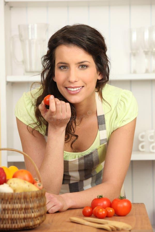 Donna che mangia pomodoro immagine stock libera da diritti
