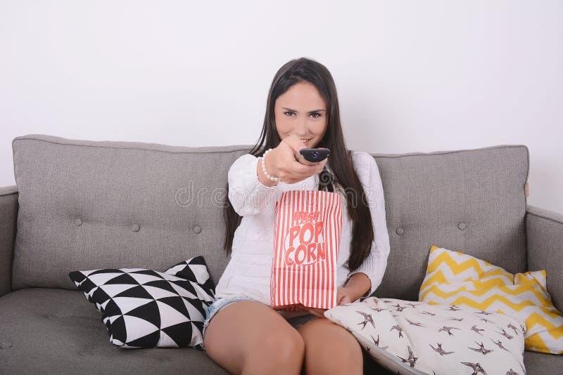 Donna che mangia popcorn e che guarda i film fotografia stock libera da diritti