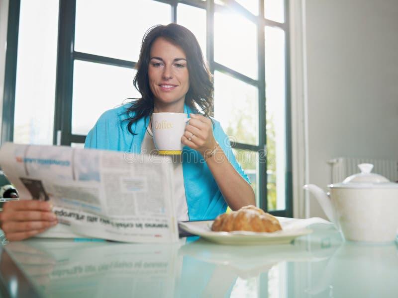 Donna che mangia prima colazione nel paese immagini stock