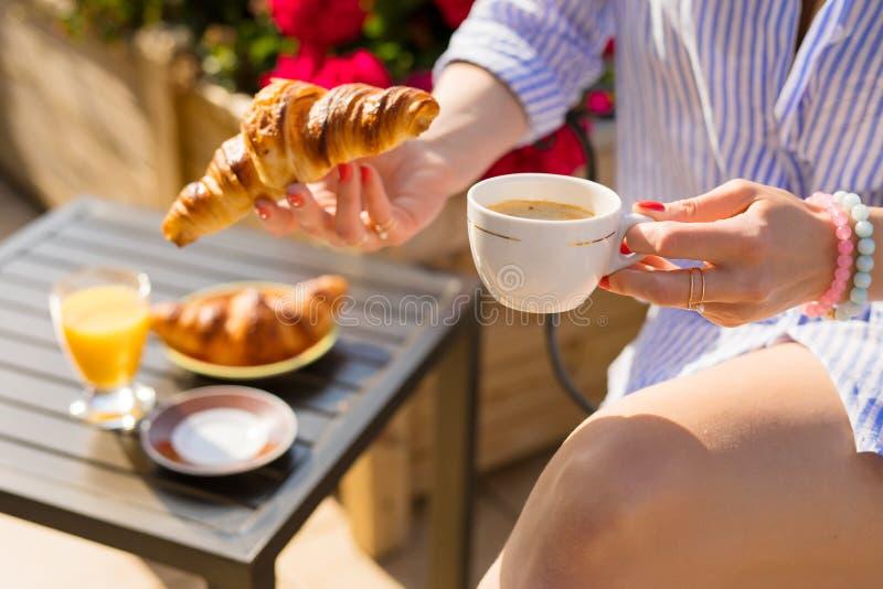 Donna che mangia prima colazione sul balcone fotografia stock libera da diritti