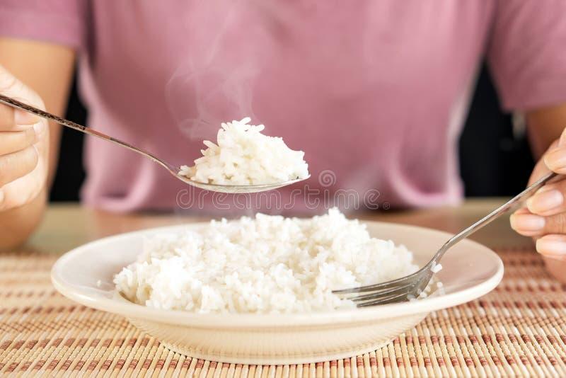 Donna che mangia riso caldo cucinato dal cucchiaio in un piatto bianco immagine stock libera da diritti