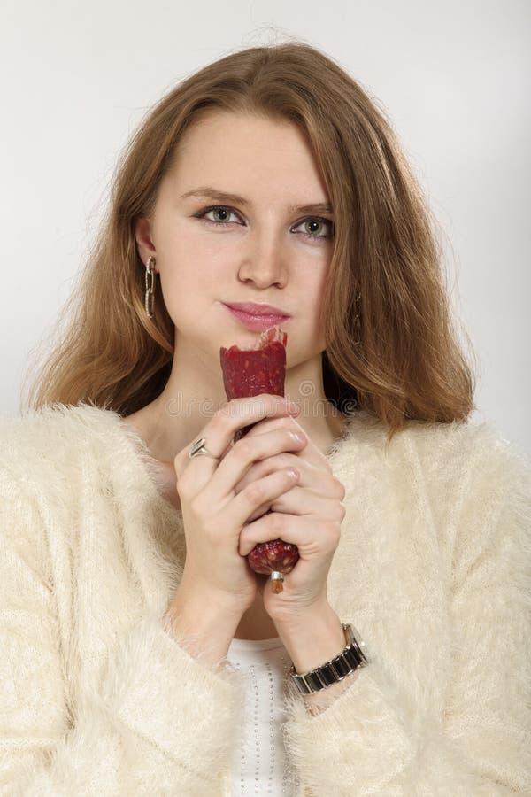 Donna che mangia salsiccia immagini stock