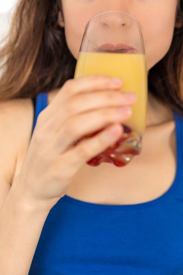 Donna che mangia un vetro del succo di frutta immagine stock