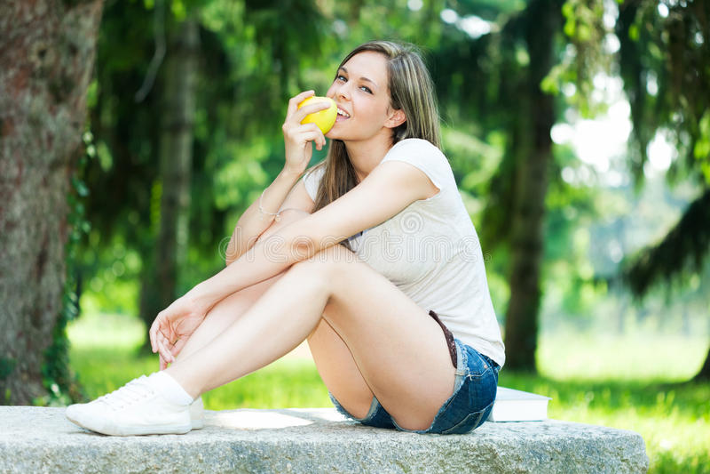 Donna che mangia una mela fotografia stock