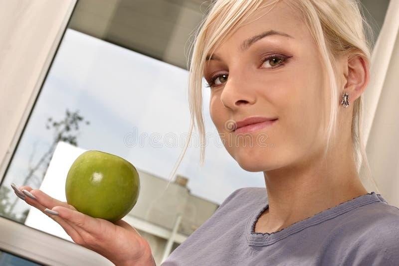 Donna che mangia una mela verde fotografia stock