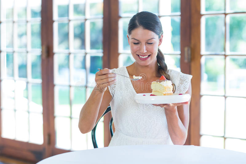 Donna che mangia una pasticceria in ristorante fotografie stock