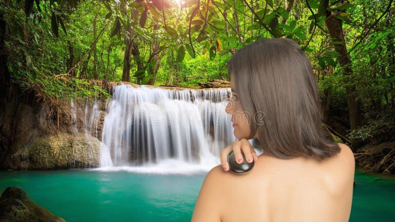 Donna che massaggia con la pietra dell'ossidiana fotografia stock libera da diritti
