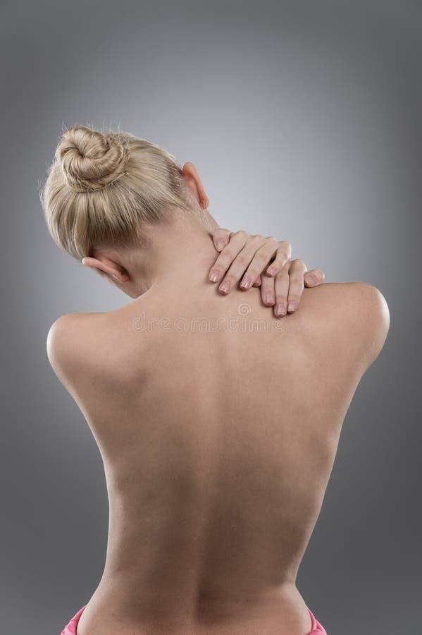 Donna che massaggia il collo e la parte posteriore di dolore fotografia stock