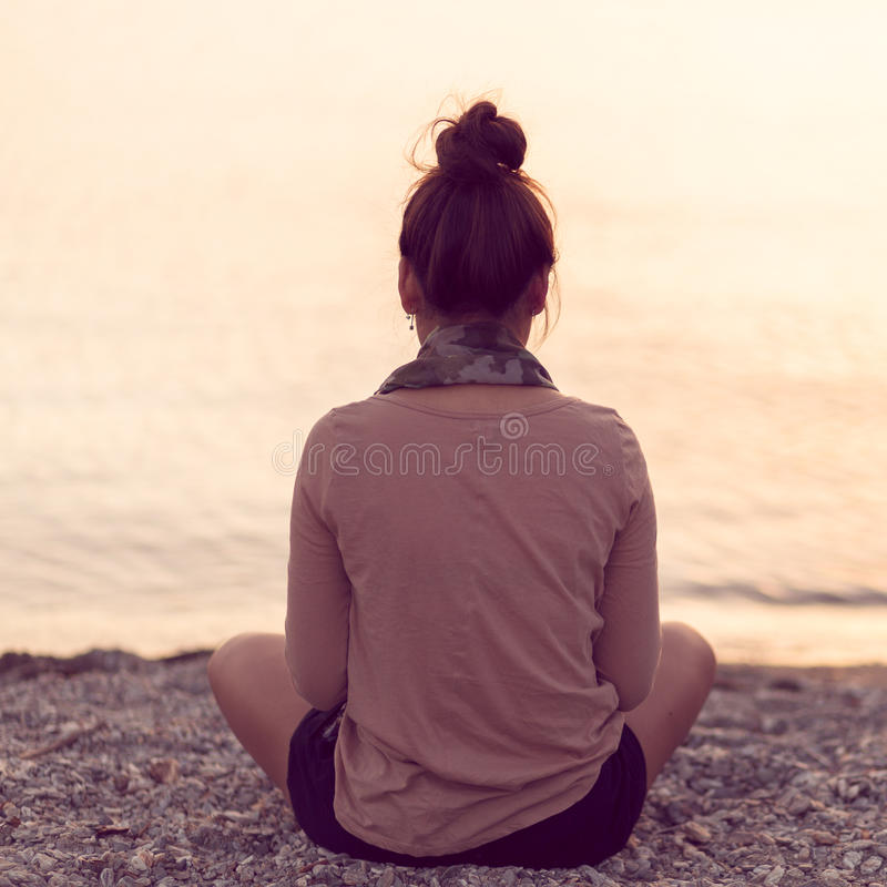 Donna che medita al tramonto sereno della spiaggia immagini stock