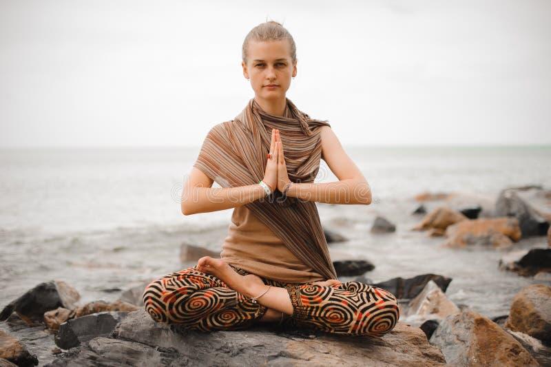 Donna che medita alla spiaggia ritirata di yoga namaste nella posa del loto immagini stock libere da diritti