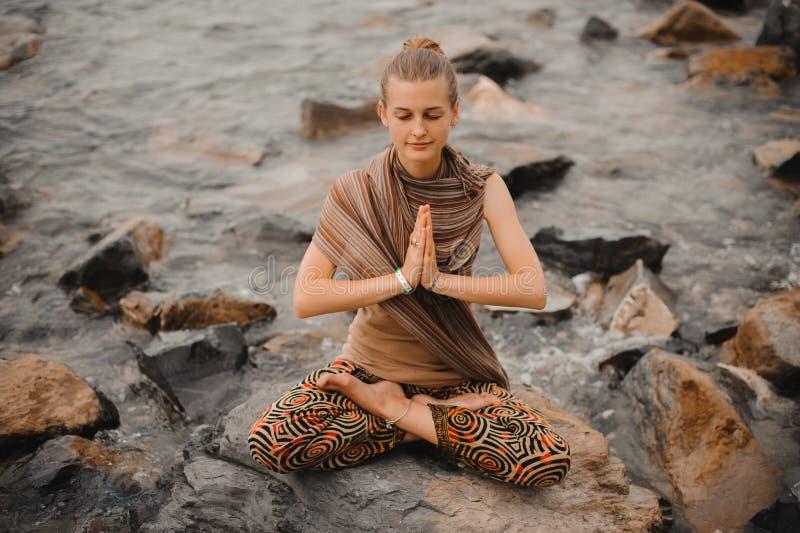 Donna che medita alla spiaggia ritirata di yoga namaste nella posa del loto fotografia stock libera da diritti