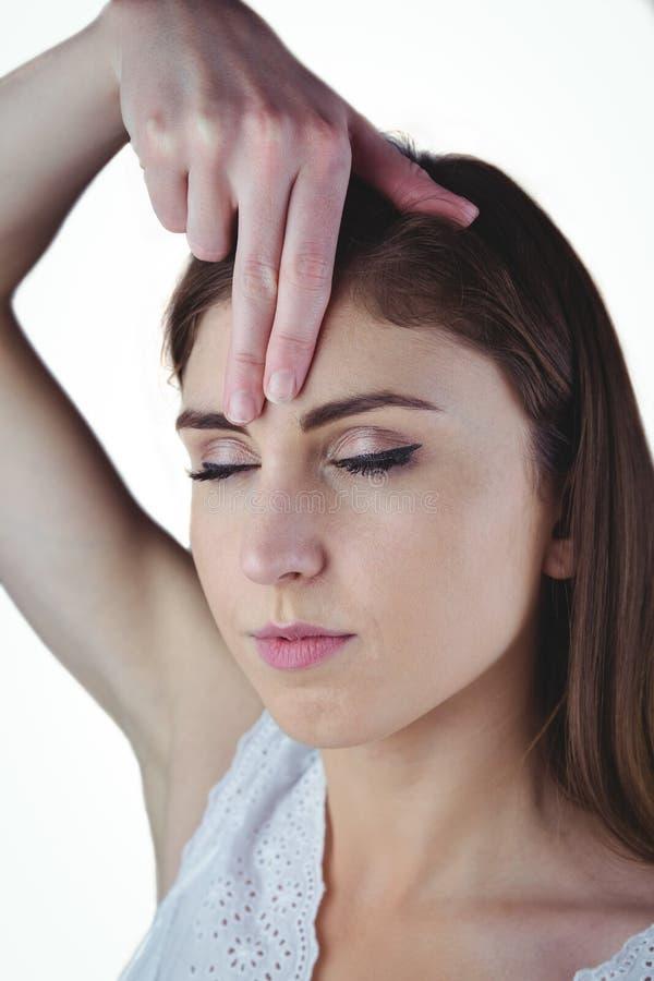 Donna che medita con la mano su fronte fotografie stock