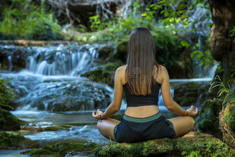 Donna che medita nella foresta che fa yoga fotografie stock libere da diritti