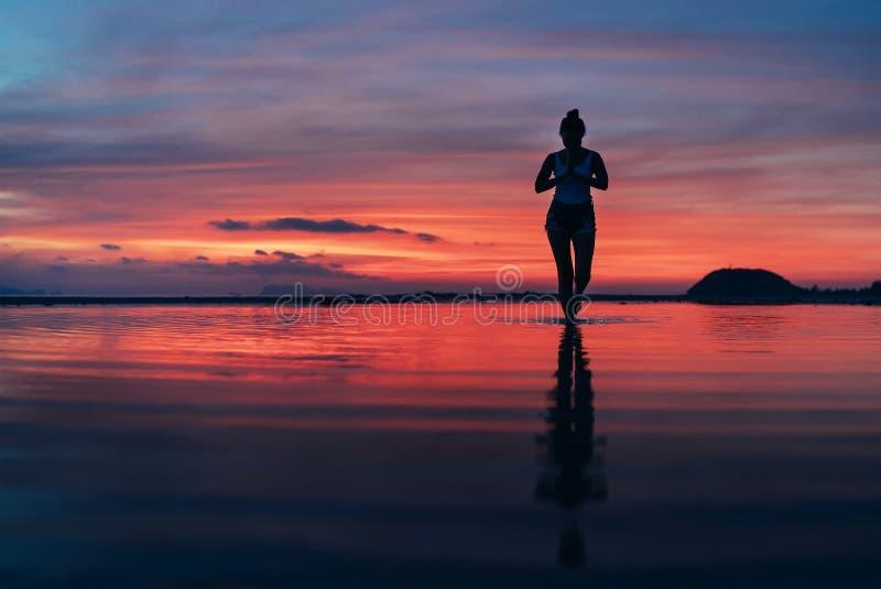 Donna che medita nella posa calma di yoga su spiaggia del mare di tramonto fotografie stock libere da diritti