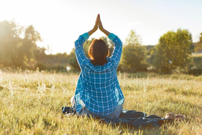 Donna che medita, yoga di pratica in natura, vista dalla parte posteriore Tramonto, paesaggi rustici, prato verde immagini stock libere da diritti