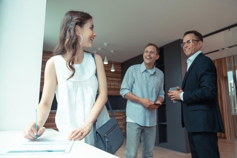 Donna che mette firma mentre comprando casa con il marito fotografia stock