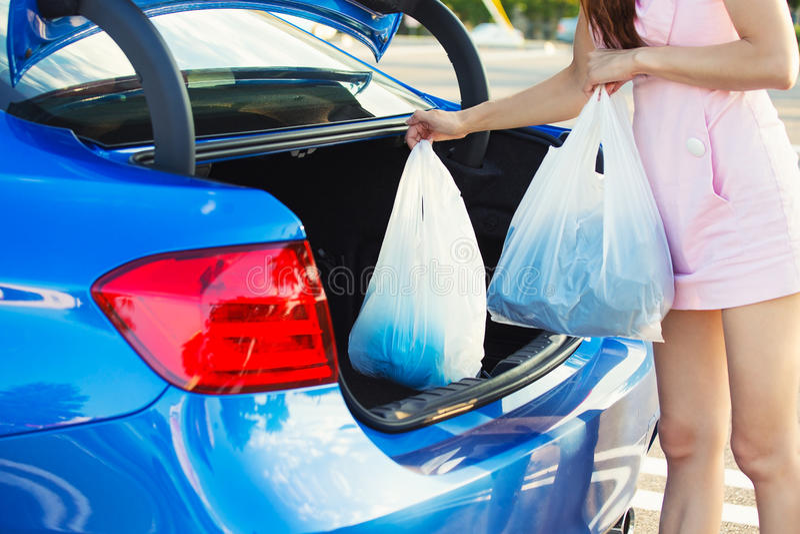 Donna che mette i sacchetti della spesa dentro il tronco dell'automobile blu immagini stock libere da diritti