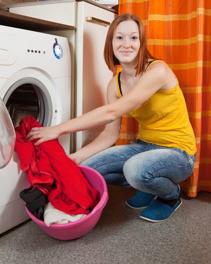 Donna che mette i vestiti nella lavatrice immagini stock libere da diritti