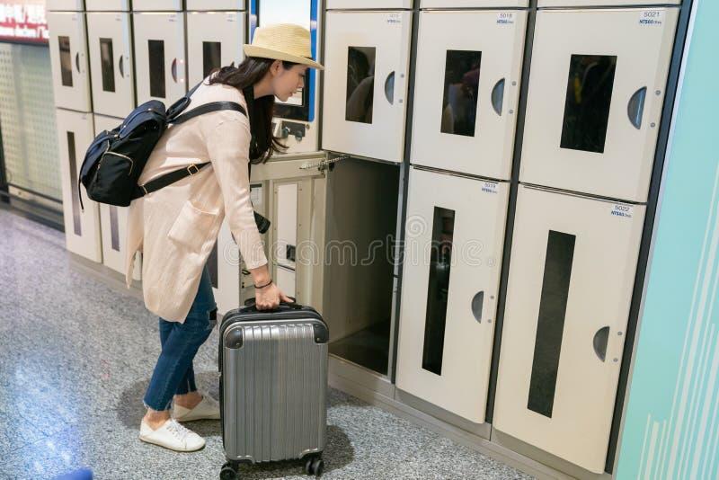 Donna che mette la sua roba in armadio elettronico immagini stock libere da diritti