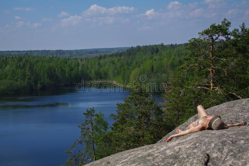 Donna che mette su scogliera un rilassamento sopra il lago Yastrebinoye, distretto nella regione di Leningrado, Russia di Priozer immagini stock