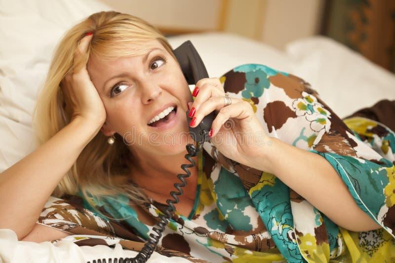 Donna che mette sul suo letto facendo uso del telefono fotografie stock libere da diritti