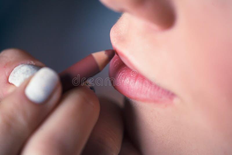 Donna che mette sul trucco, labbra di verniciatura con lipliner rosso Primo piano delle labbra commoventi con la matita fotografia stock libera da diritti