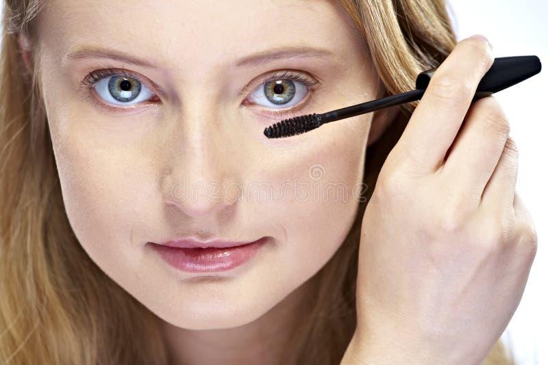 Donna che mette trucco della mascara fotografia stock libera da diritti