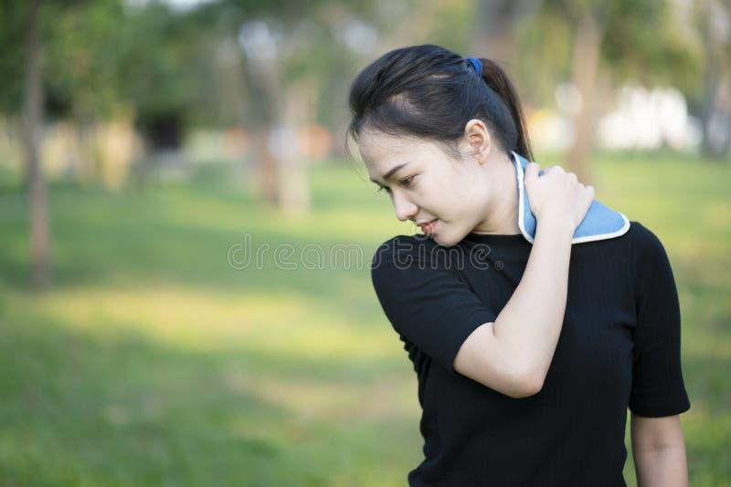 Donna che mette un pack sul suo dolore al collo fotografia stock