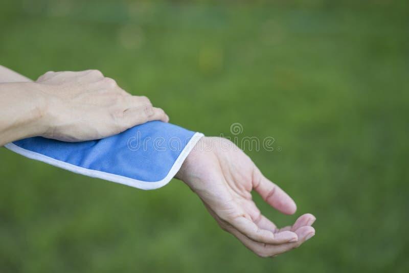 Donna che mette un pack sul suo dolore del braccio fotografia stock libera da diritti