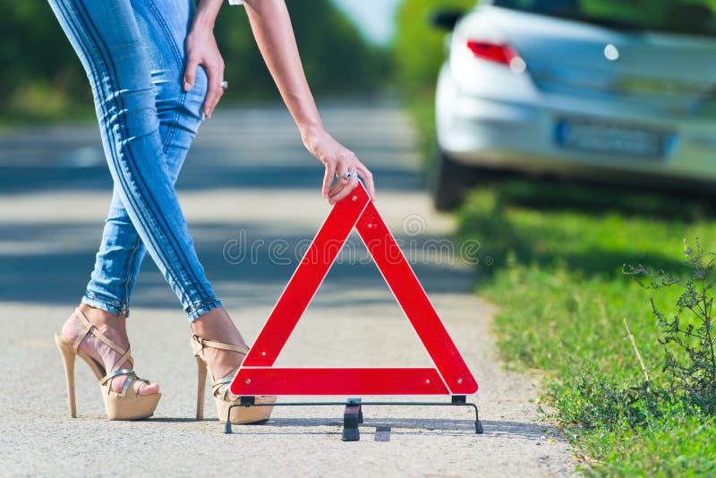 Donna che mette un triangolo su una strada immagini stock