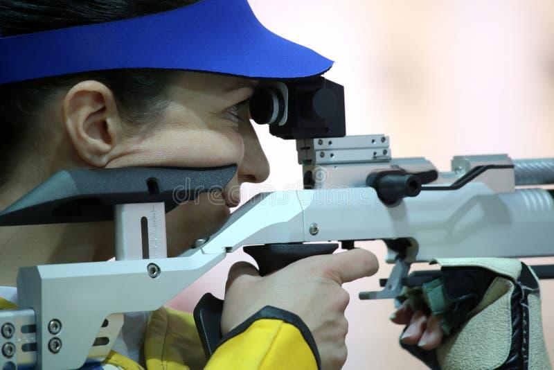 Donna che mira un fucile di aria pneumatico fotografie stock libere da diritti