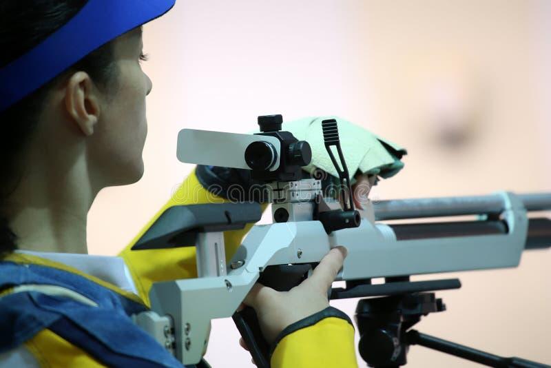 Donna che mira un fucile di aria pneumatico fotografia stock