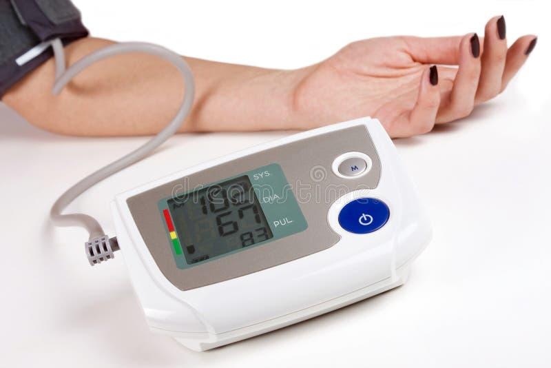 Donna che misura la sua propria pressione sanguigna fotografia stock libera da diritti