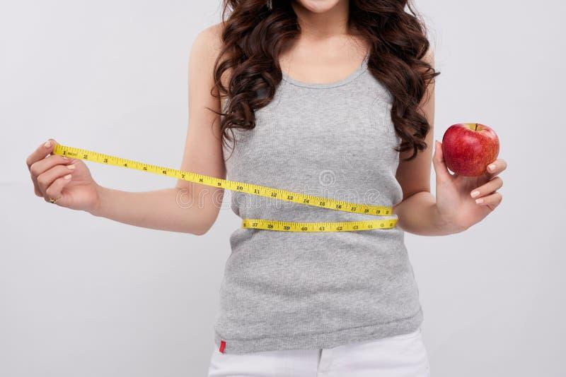 Donna che misura la sua vita dopo la dieta, mano che tiene mela rossa fotografia stock libera da diritti