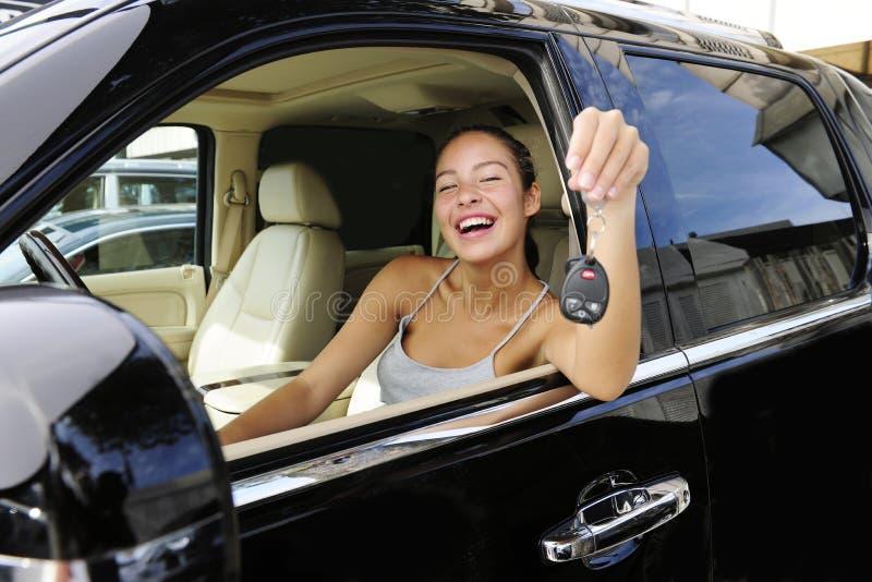 Donna che mostra i tasti del suo nuovo veicolo fuori strada 4x4 immagini stock