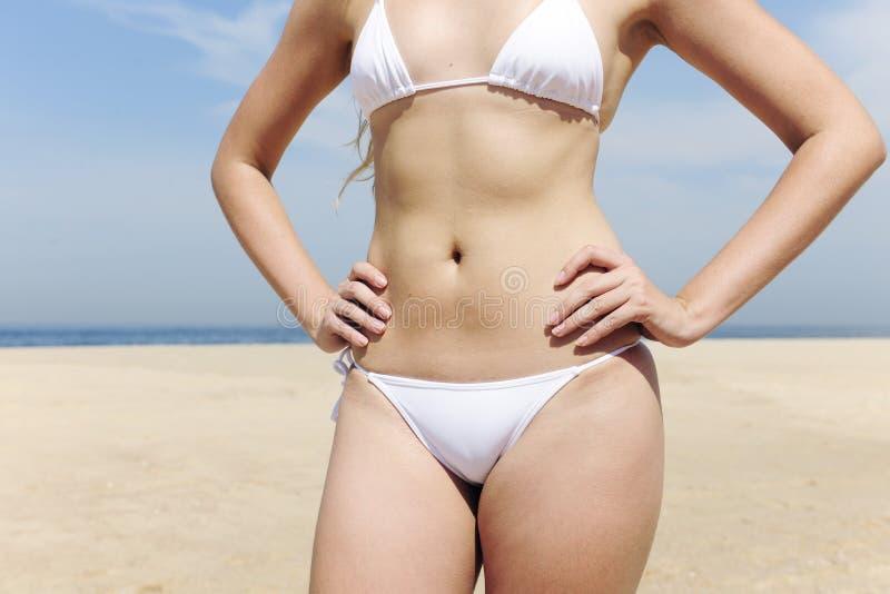 Donna che mostra il suo corpo sexy sulla spiaggia immagine stock libera da diritti