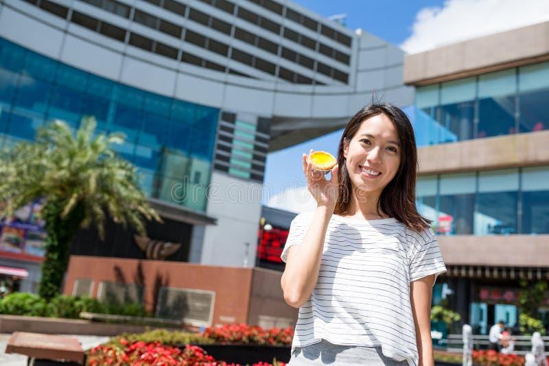 Donna che mostra la crostata dell'uovo immagine stock libera da diritti